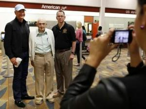 Ember Patterson, an account coordinator with Frankel Media Group, takes a photo of Bob Gasche, a 90-year-old Gainesville resident and World War II veteran, with Mark Avera, at left, and Scott Dupree at the Gainesville Regional Airport Thursday before Gasche flies to Washington, D.C., to visit the Iwo Jima Memorial. Doug Finger/The Gainesville Sun